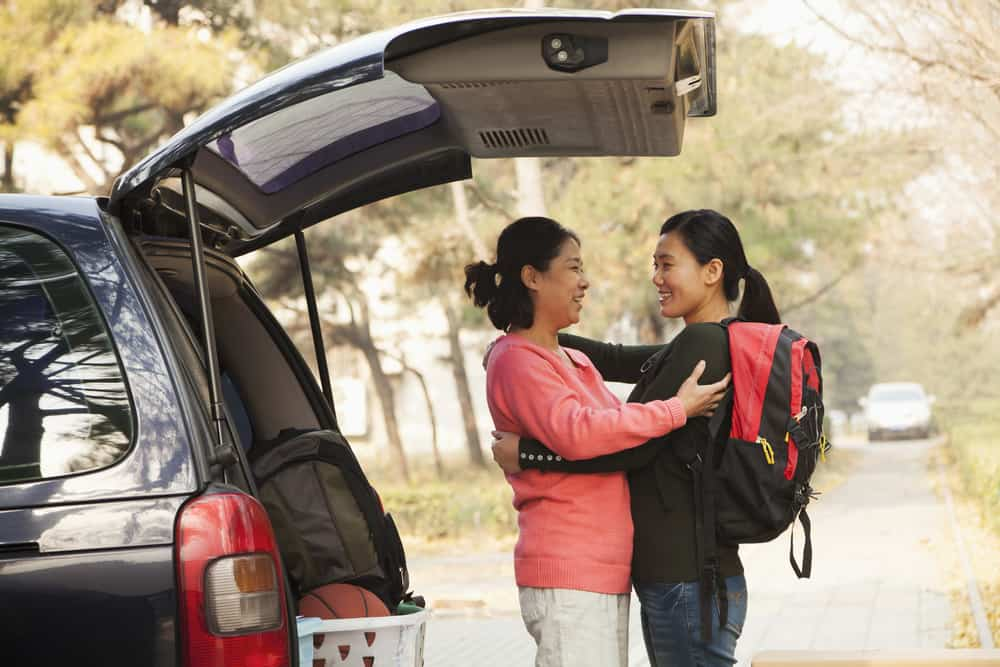 ladies hugging while packing car for school