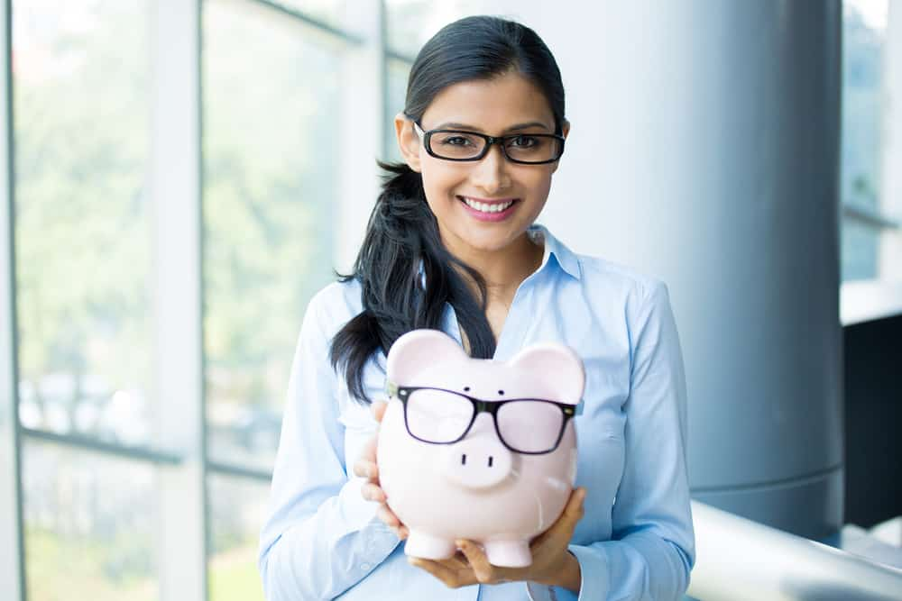 lady holding piggy bank with glasses