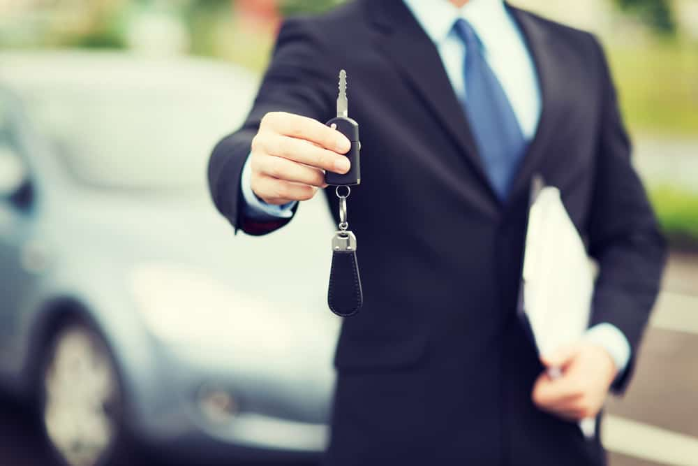 car salesman handing over new car keys