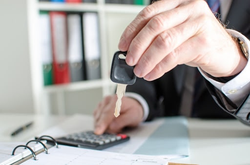 using a car loan calculator and holding key