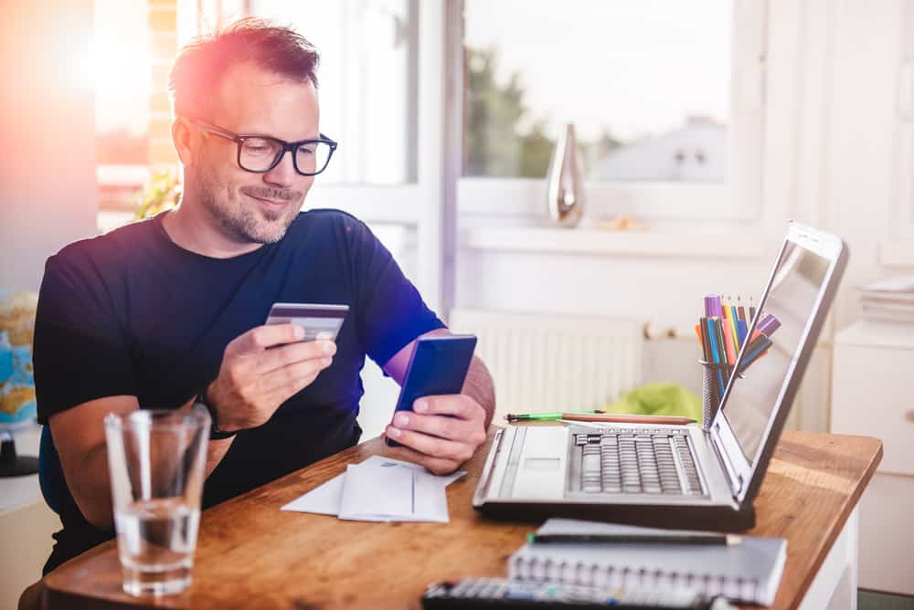 smiling man holding phone and credit card