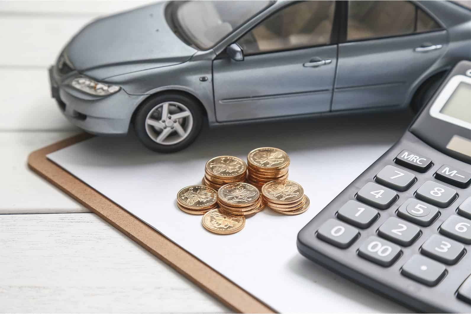 coins next to car model and calculator