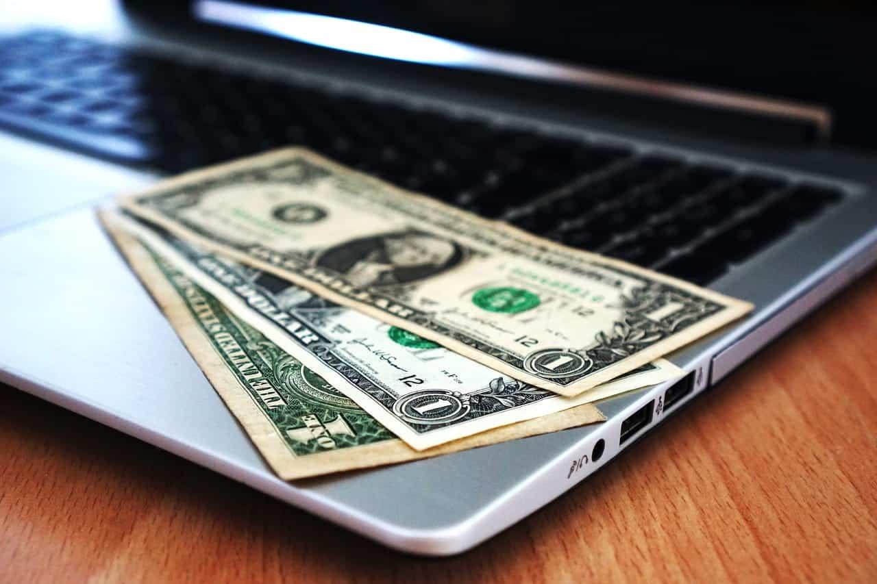 money bills on laptop